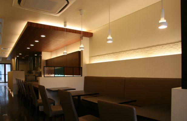 入ってすぐの客席。 背に照明を入れ、のっぺりした壁にタイルで陰影をつけます。