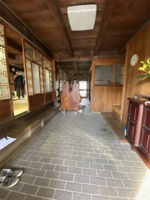 リフォーム前の通り土間の玄関。中庭まで抜けています。ガラスの入った建具のみで外部と区切られており、外気温と同じ状態です。ダイニングキッチンが向かって右側。不便なので床でつなげたいとのご希望でした。