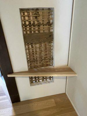 廊下から突き当たった壁の向こうがペットエリアです。気配が感じるようにしたいと、土壁を少し落として小窓に。杉板の飾棚を取り付けました。
