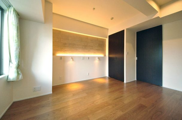 主寝室のヘッドボードに照明を入れ、横になってもまぶしくない灯り。この壁にもエコカラットを貼っています。
