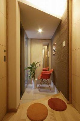 玄関のニッチと天井の間接照明。 玄関扉H2200のスライドドアに天井高さを合わせ すっきりと納め、床は汚れにくい大判磨きタイル。
