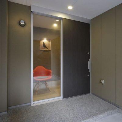 ガレージ奥の玄関。 LEDのブラケットで夜間付けっぱなしでも省エネです。スライドドアの袖から玄関のニッチが見えます。