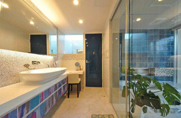 広い洗面脱衣室と、奥はトイレです。さまざまなタイルを貼り分け、 カラーガラスを壁に塗り込みました。