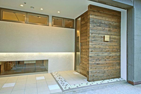 店舗のファサード レッドシダーの外壁用パネルと塗り壁の外観です。