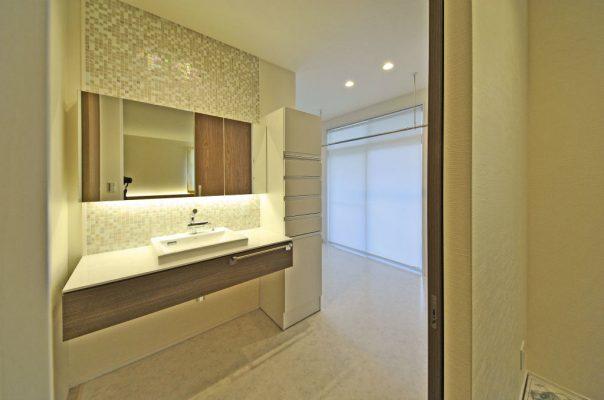 ダイニングと寝室からつながっている洗面所。奥はユーティリティーで、掃出し窓の外は物干バルコニー。アイロンがけもできます。