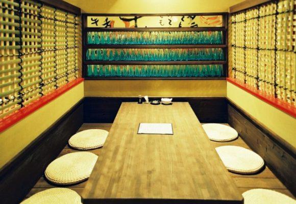 1階のテーブル席。壁には酒瓶を貼り付けました。 こちらもオーナーのアイデアです。