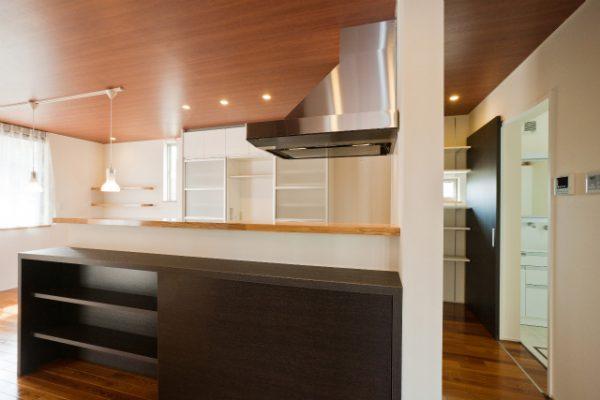 I型のキッチンの背面に制作した棚。 吊扉は半分はオープンになっています。